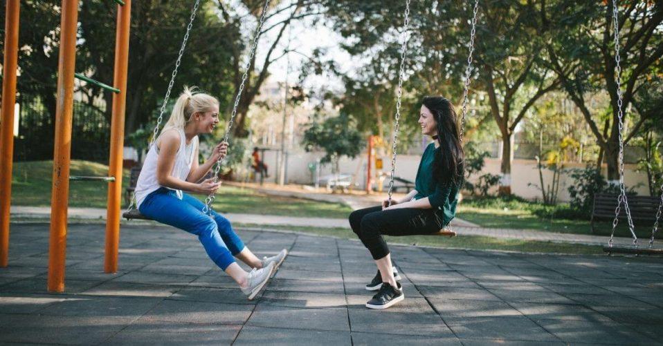 two people sat on swings talking