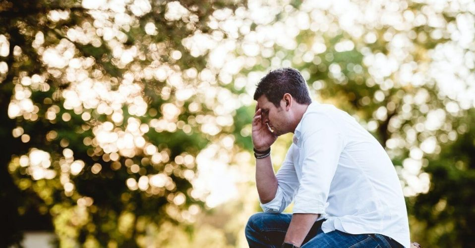 man looking sad in front of some trees in a white shirt