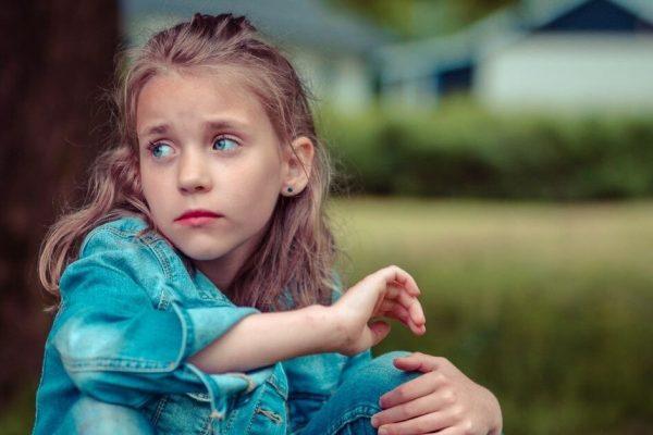 girl in denim sat on grass looking sad