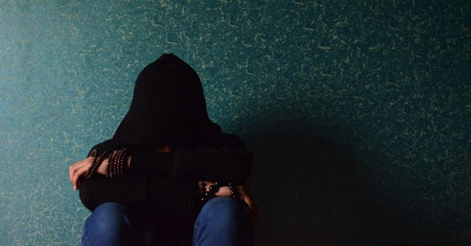 person in black hoodie with hands face in knees